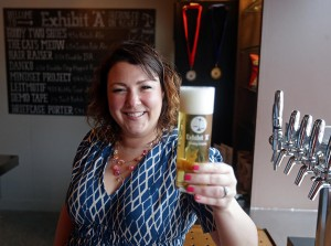 (Framingham, MA 04/26/17) Executive Director of the Mass Brewers Guild Katie Stinchon pictured with a glass of Goody Two Shoes Kolsch style beer at the Exhibit 'A' Brewing Company tap room in Framingham. Wednesday, April 26 2017. Staff photo by John Wilcox.